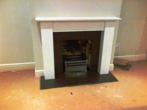 Limestone fireplace in Guildford with honed black granite slips and hearth